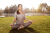 Woman relaxing in Lotus yoga pose - MFF003060