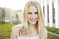 Portrait of smiling young blond woman outdoors - MFF003081