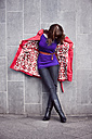 Young woman with colorful clothing opening her patterned coat - MFF003108