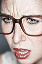 Close up of angry female face with freckles and glasses - MFF003117