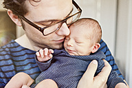 Close-up of father cuddling his newborn son - MFF003132