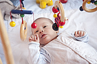 Baby lying down looking at wooden toys - MFF003144