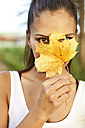 Woman holding up an autumn leaf in front of her face - MFF003168