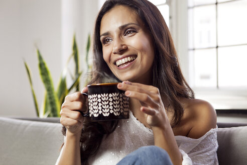 Smiling woman relaxing on couch holding a mug - MFF003171