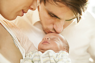 Close-up of parents kissing and holding their newborn baby - MFF003186