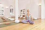 Smiling woman sitting in yoga studio - MFF003204