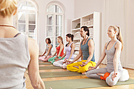 Group of people in yoga studio sitting in Lotus pose next to instructor - MFF003207