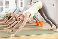 Group of people in yoga studio holding down dog pose - MFF003213