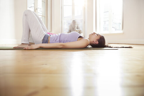 Woman in sunny yoga studio relaxing on her mat - MFF003237