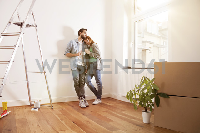 Smiling young couple having a coffee break in new apartment - MFF003261
