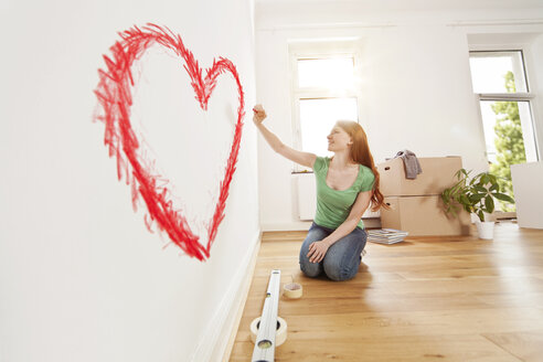 Young woman drawing a heart on a wall in new apartment - MFF003267