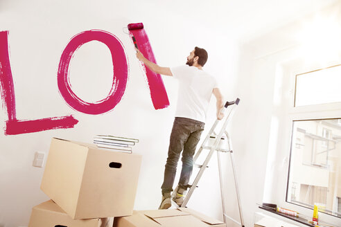 Young man painting the word LOVE on a wall in new apartment - MFF003270