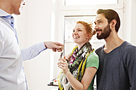 Young couple receiving house key from real estate agent - MFF003285