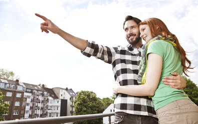 Smiling young couple hugging on balcony in the city - MFF003291