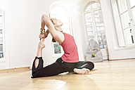 Woman in yoga pose stretching herself - MFF003324