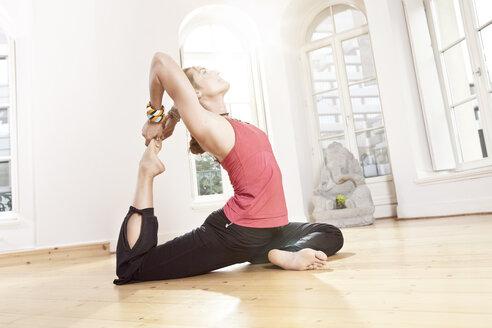 Woman in yoga pose stretching herself - MFF003324