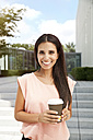 Portrait of smiling woman holding takeaway coffee outdoors - MFF003339