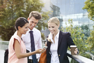 Smiling businesswoman showing cell phone to colleagues - MFF003342