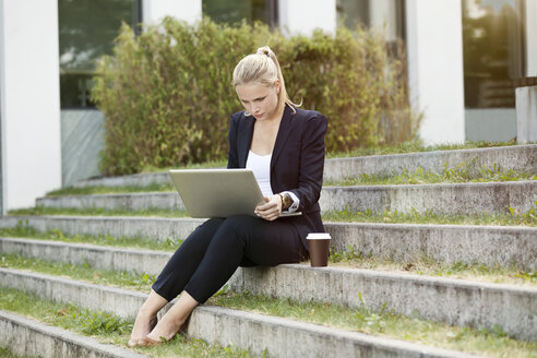 Young businesswomen sitting on stairs outside using a laptop - MFF003345