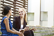 Two businesswomen talking outside during a coffee break - MFF003348