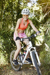 Young woman riding mountainbike on a trail - MFF003351