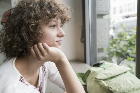 Young woman looking through window - TAMF000631