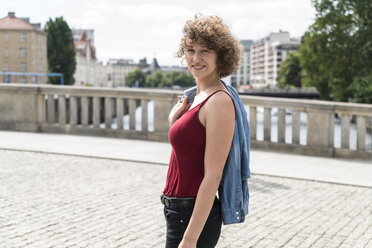 Germany, Berlin, portrait of smiling young woman - TAMF000643