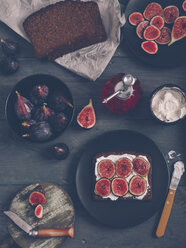 Toasted rye bread with cream cheese, sliced figs and olive oil on dark wood - RTBF000338