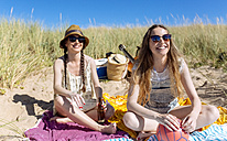 Portrait of happy teenage girl having fun with her best friend on the beach - MGOF002365