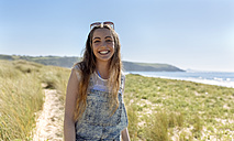 Portrait of happy teenage girl on the beach - MGOF002368