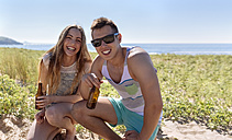Happy friends with beer bottles on the beach - MGOF002377