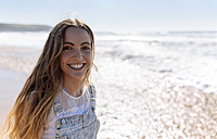 Portrait of happy teenage girl on the beach - MGOF002392
