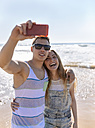 Young couple in love taking selfies on the beach - MGOF002395