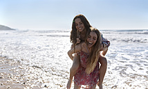 Teenage girl giving her best friend a piggyback ride on the beach - MGOF002404