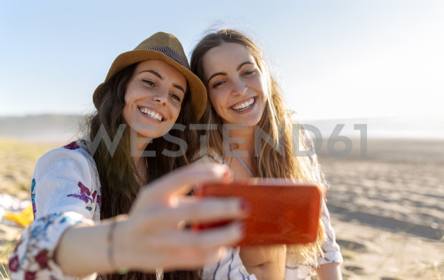 Two best friends taking selfie with smartphone on the beach - MGOF002431 - Marco Govel/Westend61