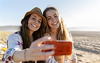 Two best friends taking selfie with smartphone on the beach - MGOF002431