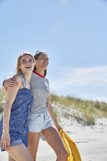 Two happy female friends walking on the beach - SRYF000028