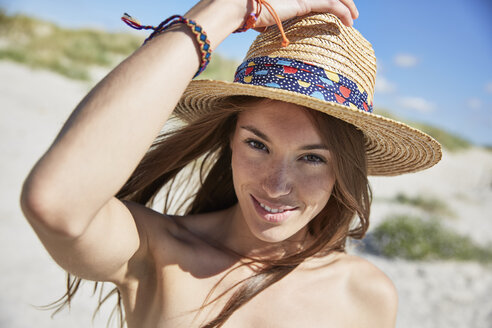 Portrait of smiling young woman wearing straw hat on the beach - SRYF000058