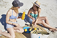 Two female friends on the beach enjoying healthy snack - SRYF000064