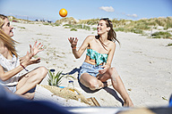 Two female friends on the beach throwing an orange - SRYF000067