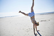 Young woman doing a handstand on the beach - SRYF000073