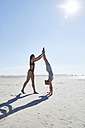 Young woman helping friend doing a handstand on the beach - SRYF000076
