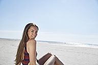 Smiling young woman sitting on the beach - SRYF000079