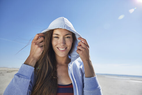 Smiling young woman wearing hoodie on the beach - SRYF000082