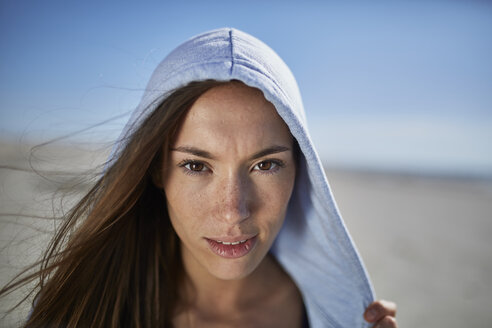 Smiling young woman wearing hoodie on the beach - SRYF000085