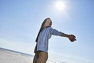 Happy young woman with outstretched arms on the beach - SRYF000088