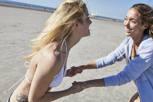 Two female friends having fun on the beach - SRYF000094