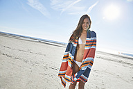 Smiling young woman in bikini with blanket on the beach - SRYF000136