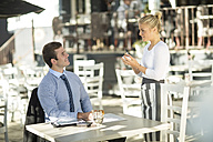 Businessman and waitress at outside restaurant - ZEF010066