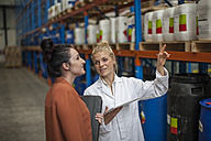 Woman with digital tablet in warehouse talking to woman - ZEF010132
